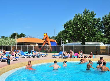 View of the edge of the swimming pool with its deckchairs at the La Prairie campsite in Vendée in Saint-Hilaire
